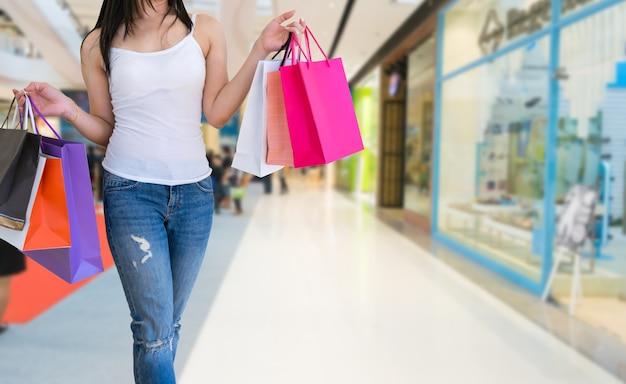 Женщина ходит руками, держа сумки в торговом центре