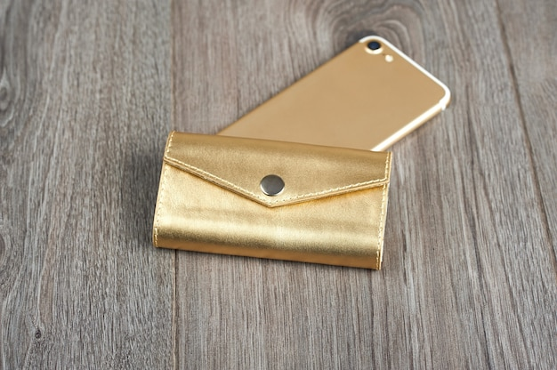 Female wallet and smartphone on the brown wooden surface. looks very fashionable and stylish.
