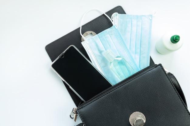電話、消毒剤、医療マスク、白い背景、上面図、分離された女性の財布