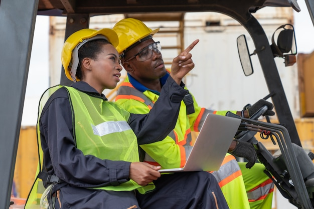 Female warehouse logistic staff points with the finger near a male worker driving a forklift