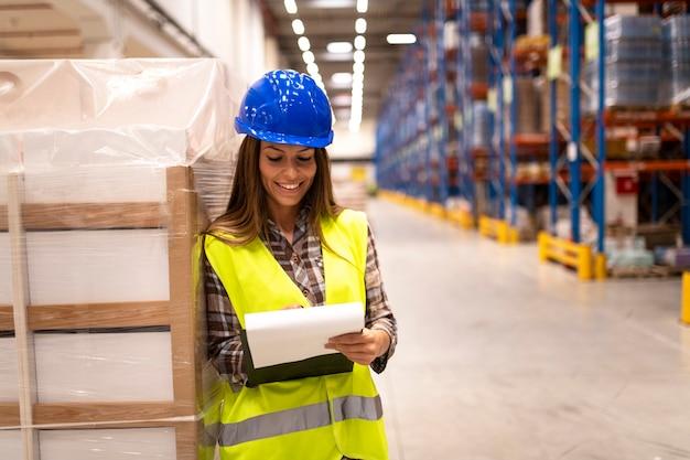Magazziniere femminile che controlla la fornitura nell'area di stoccaggio del magazzino di grande distribuzione