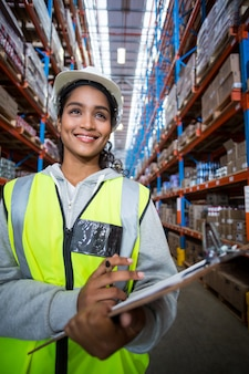 Female warehouse worker holding on clipboard