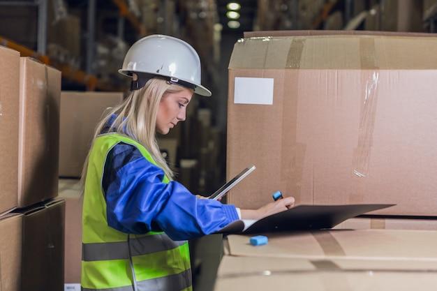Работница склада делает заметки в документах возле ящиков с товарами