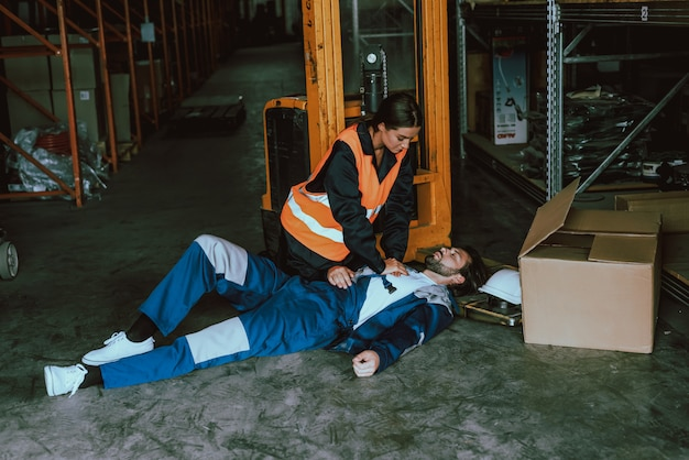 Female warehouse worker providing first aid to man