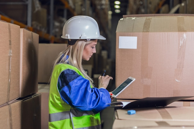 Работница склада с помощью планшетного пк возле коробок с товарами