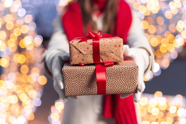 Female in warm clothes showing christmas gifts
