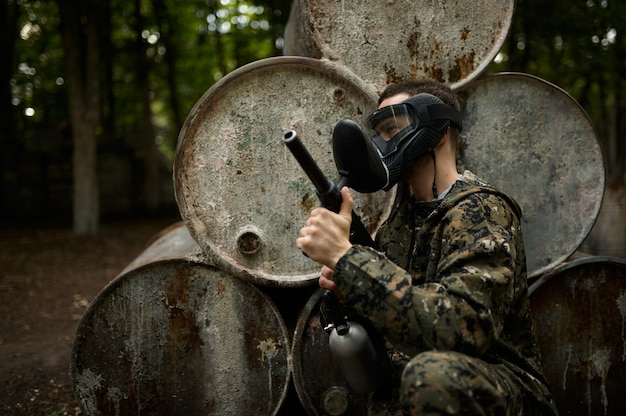 Female warrior in camouflage and protection mask holds paintball gun. extreme sport with pneumatic weapon and paint bullets or markers, military team game outdoors, combat tactics