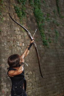 Female warrior shooting from bow at sky.