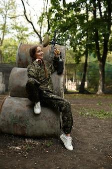 Женщина-воин с пейнтбольным ружьем позирует на ржавых бочках в лесу