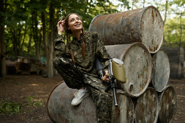 Female warrior with paintball gun poses on rusty barrels in the forest. extreme sport with pneumatic weapon and paint bullets or markers, military team game outdoors, combat tactics