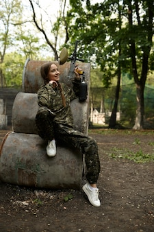 Female warrior with paintball gun poses on rusty barrels in the forest