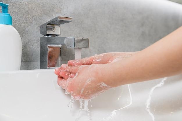 세계 대유행 코로나바이러스 기간 동안 집 화장실 세면대에서 청소용 젤을 사용하여 미생물과 바이러스로부터 여성의 팔을 씻는다