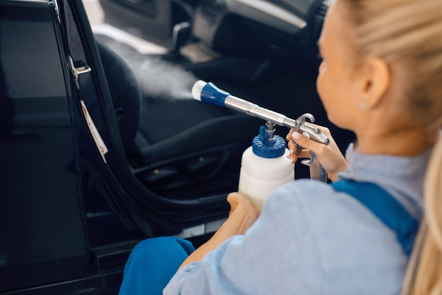 Женская стиральная машина чистит салон автомобиля, автомойка