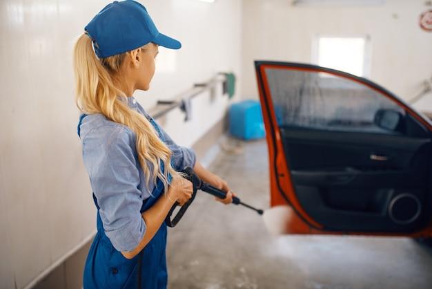 Female washer in uniform cleans door with high pressure gun in hands