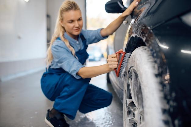 Женская шайба с щеткой в руке очищает колесо в пене, автомойка. женщина моет автомобиль, автомойку, автомойку