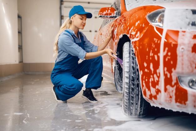 Женская шайба с щеткой в руке очищает колесо в пене
