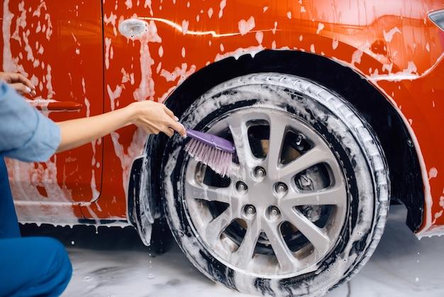 손에 브러시가 달린 여성 세탁기는 거품의 바퀴를 청소합니다.