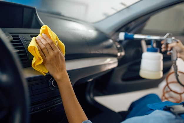 Female washer with sponge cleans car interior