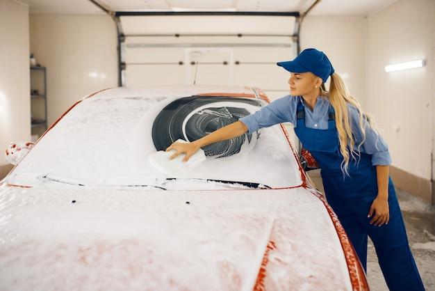 Женский омыватель с губкой протирает лобовое стекло автомобиля