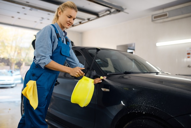 Female washer with wax spray cleans automobile, waxing on car wash service. woman washes vehicle, carwash station, car wash business