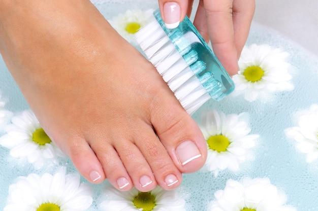 Женщина моет и чистит ногти на ногах в воде с помощью очищающей щетки.