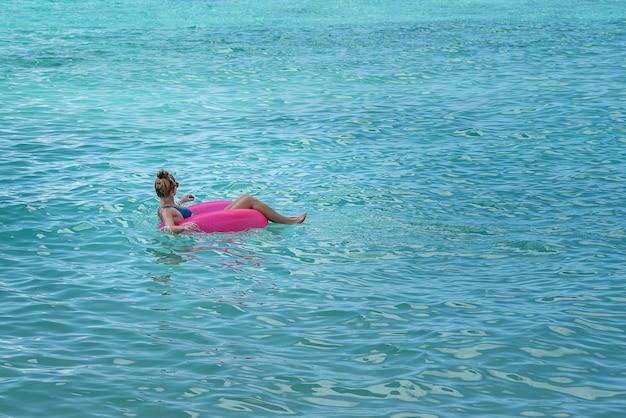 Женщина в бикини в розовом поплавке в море