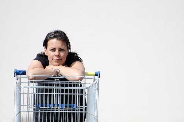 白い背景のショッピングカートに寄りかかって黒いシャツを着ている女性
