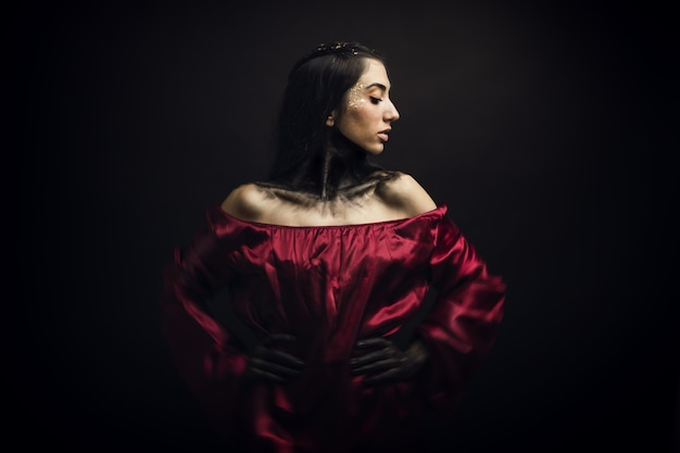 赤いドレスと黒い背景の前で彼女の顔と手に怖い化粧をしている女性