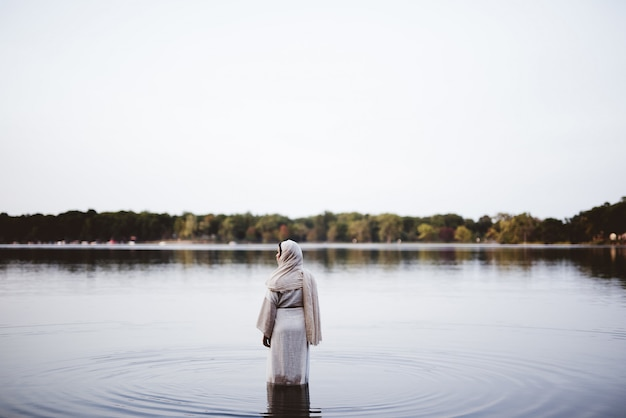 Female wearing a biblical robe while standing in the water - concept cleaning her sins