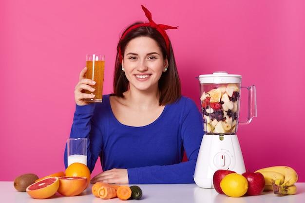 青いスウェットシャツと赤いヘッドバンドを身に着けている女性、彼女の健康のために栄養価の高い有用な混合物のガラスを保持