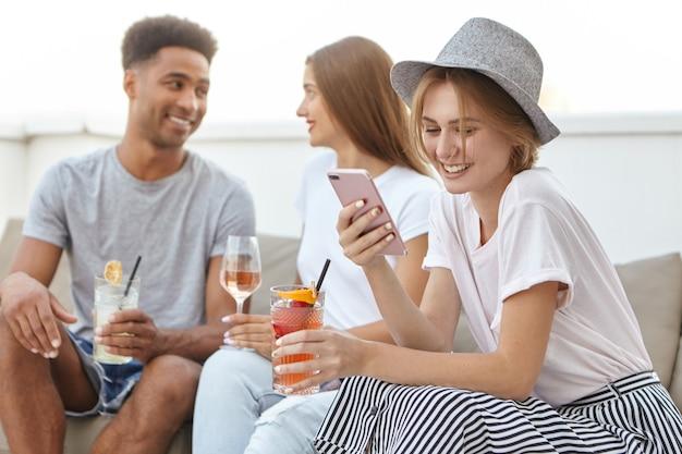 帽子と彼女の恋人からのメッセージを受信するエレガントな服を着ている女性