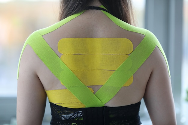 Female wearing kinesio tapes at her back and shoulders at doctor office