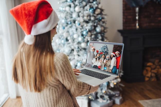 Donna che indossa il cappello della santa mentre parla con un amico in linea sul computer portatile