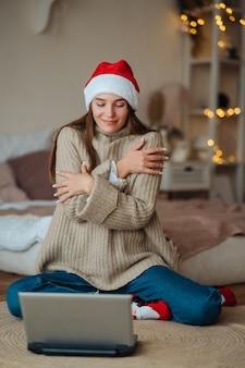 Donna che indossa santa sorridente mentre parla con un amico in linea sul computer portatile durante la celebrazione del natale a casa
