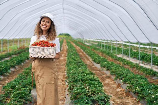 Женщина в белой кепке и фартуке собирает клубнику