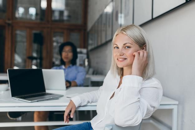 Женский веб-разработчик позирует с улыбкой в офисе, пока ее азиатский коллега-мужчина работает над проектом. китайский маркетолог с помощью ноутбука сидит за столом с симпатичным европейским менеджером.