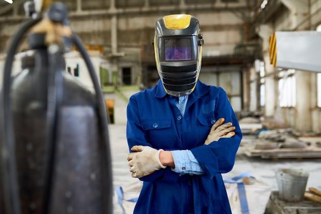 공장에서 포즈를 취하는 여성 용접기