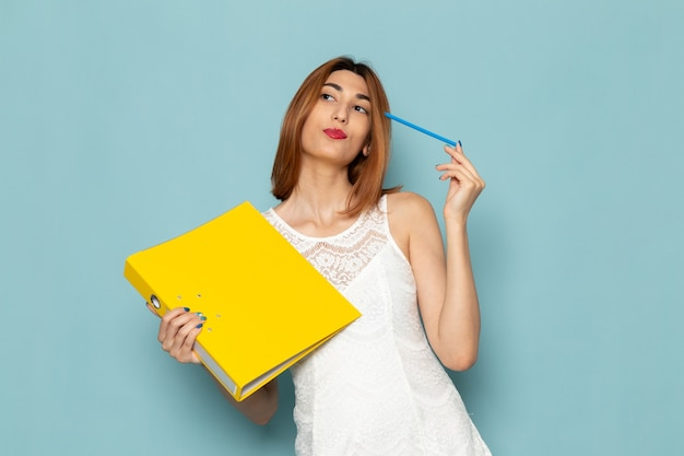 Female in white blouse and blue jeans holding yellow files