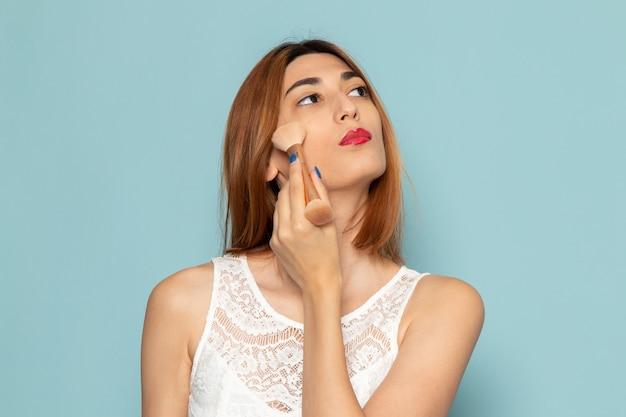 Female in white dress doing make-up