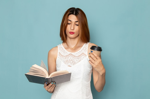 Female in white dress holding coffee cup and reading a book