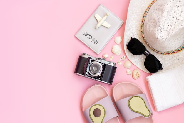 Female white hat passport black sunglasses old vintage retro camera flipflops with avocado towel toy plane seashells isolated on a light color pink wall