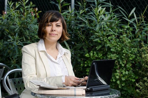 Female in a white suit sitting at a table with her laptop near the green bushes