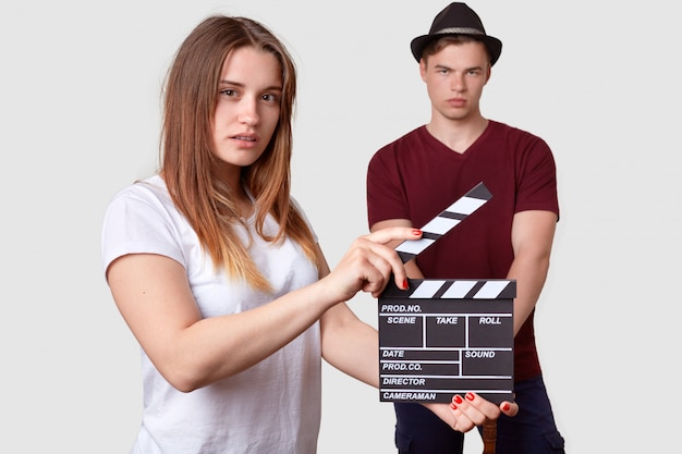 Female in white t shirt holds clapper board, shoots scene, serious stylish man stands in foreground, wears stylish headgear and t shirt, involved in film production. movie making concept