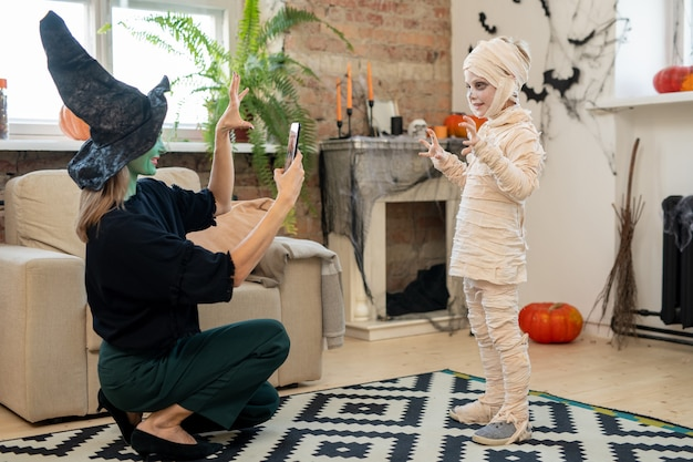 Female in witch costume taking photo of her little son