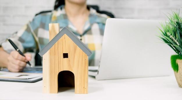 机の上にペンとラップトップコンピューターと小さな木の家を持つ女性