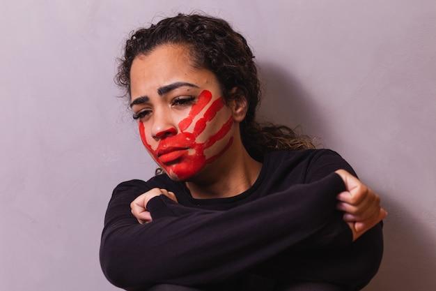 여성에 대한 폭력을 보여주는 입에 지문이 있는 여성. 배경에서 가정 폭력과 학대에 항의하는 여성.