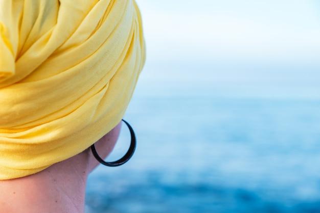 海の景色を楽しむ黄色のスカーフを持つ女性-コンセプト:癌との戦い