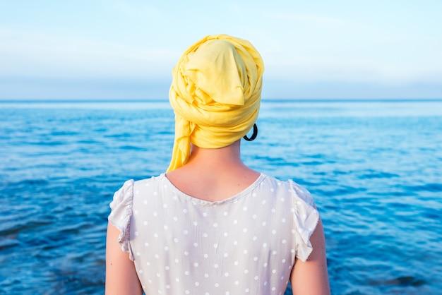 바다 전망을 즐기는 노란색 스카프를 두른 여성