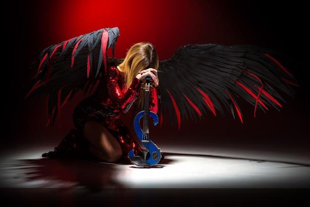 Женщина с крыльями ангела молится на коленях на полу
