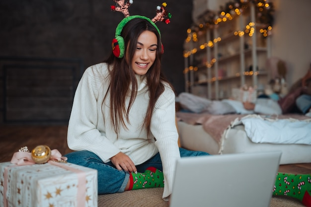 집에서 크리스마스 축하 기간 동안 노트북에 온라인 친구와 이야기하는 동안 웃고 뿔을 가진 여성